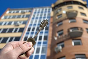 Bradford Condo owner with key in and in front of building.